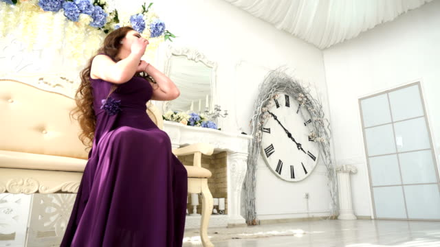 Young girl in an evening dress purple sitting on couch in luxury Interior video