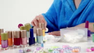 Young girl in bathrobe doing manicure at home painting nails closeup video