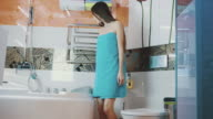 Young girl in blue towel walk in bathroom opening water faucet. Touch the water video