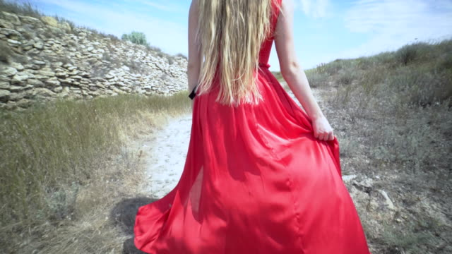 Young girl in red dress walking barefoot on a path along old stone wall video
