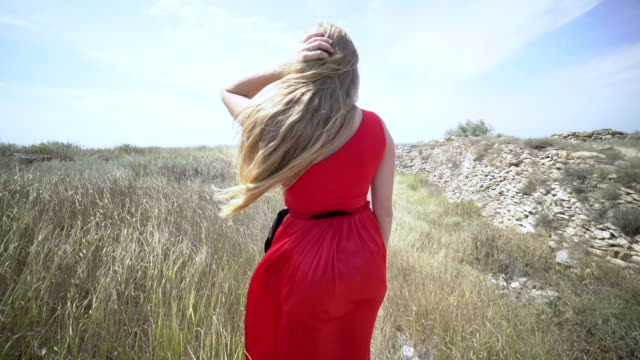 Young girl in red dress walking barefoot on a path towards the sea video