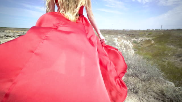 Young girl in red dress walking barefoot on the footpath along old stone wall video