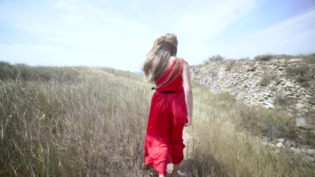 Young girl in red dress walking barefoot on the footpath towards the sea video