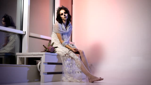 Young girl in white dress and veil participating in halloween party sitting in the room. with creative scary creepy make-up is on the bench near the window. appearance the flower video