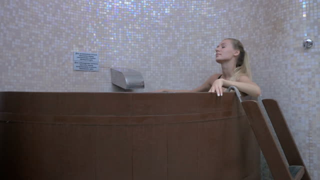 Young girl is relaxing in the wooden bath after the sauna video