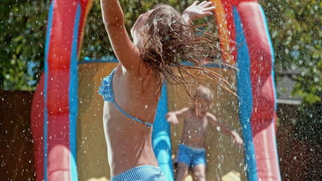 SLO MO Young girl jumping over a water sprinkler video