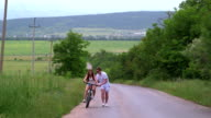 Young girl learning to ride bicycle on country road video