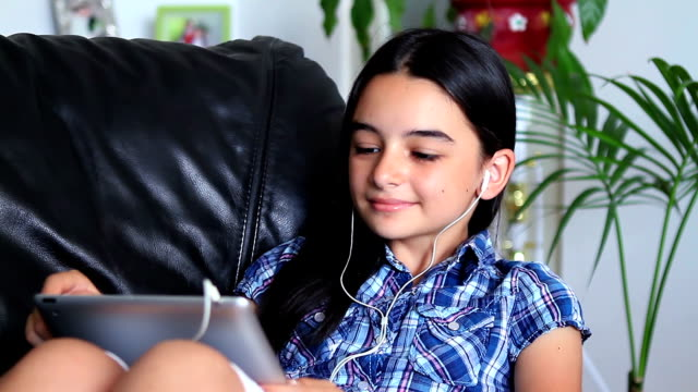 Young girl listening music on tablet PC. video