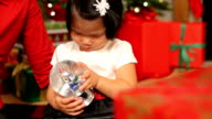 Young girl looking at Christmas snow globe video