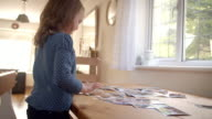 Young Girl Looking At Family Photographs On Table At Home video