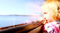 Young girl looks out train window at the scenery video
