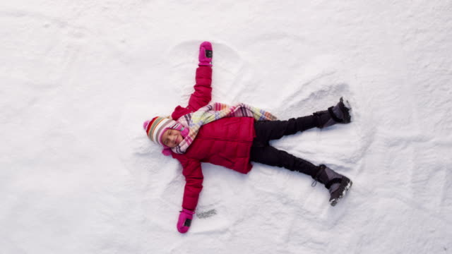 Young girl making snow angel in winter video