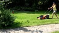 Young girl mowing green grass lawn with orange push mower. FullHD video