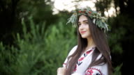 A young girl of Slavic appearance with a wreath of wild flowers on the MidSummer. video