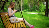 Young girl on a swing, reads the tablet pc video