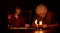 A young girl painting with her grandmother by the light of candles video