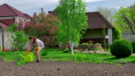 Young girl planting flowers on the lawn video