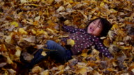 Young girl playing in fall leaves, slow motion video