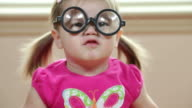Young girl playing with silly glasses video