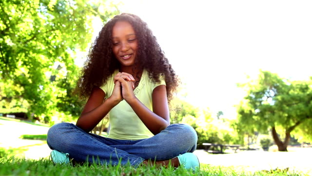 Young girl praying in the park video