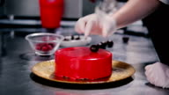 A young girl puts chocolate spheres on a cake. video