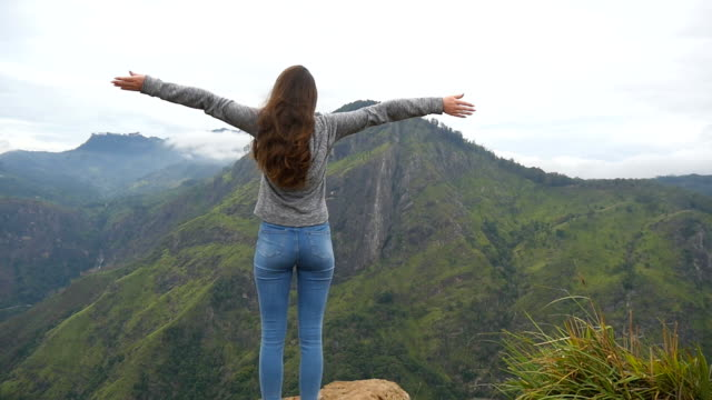 Young girl reaching up top of mountain and raised hands. Woman tourist standing on the edge of beautiful canyon, victoriously outstretching arms up. Slow motion Rear back view video