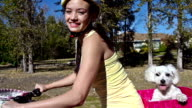 Young girl riding bicycle with pet dog video