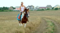 Young girl riding horse across the field from village video