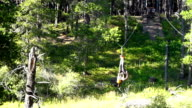 Young girl riding zip line across ravine upside down video