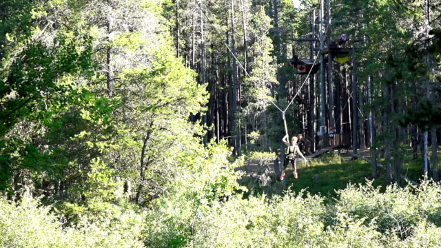 Young girl riding zip line across ravine video