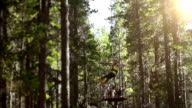 Young girl riding zip line in forest video