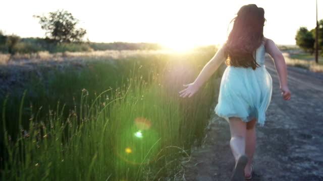Young Girl Running at Sunset Through Tall Grass video