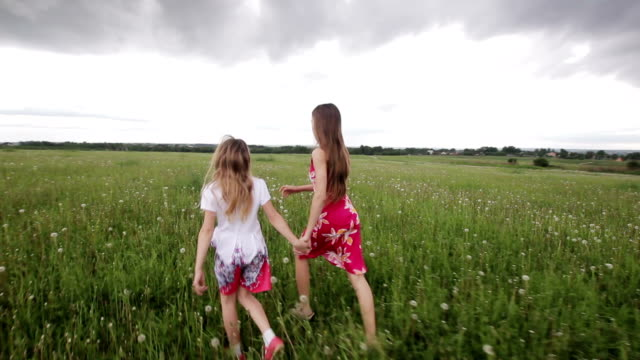 Young girl running in a field holding hands video