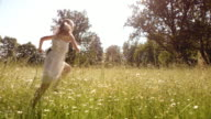 SLO MO Girl running in high grass on sunny day video