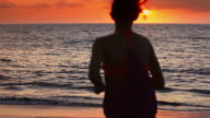 Young girl running towards the ocean at sunset video