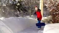 Young girl Shoveling snow on walkway video