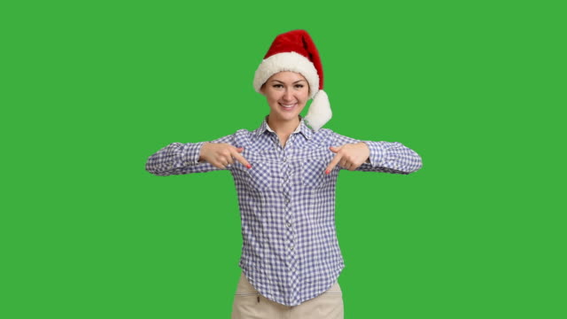 young girl shows copy space in shirt and santa hat on a green screen video