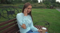 A young girl sits on a park bench holding a drink and talk on the phone video