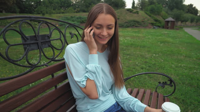 A young girl sits on a park bench, holding a drink and talking on the phone, smiles video