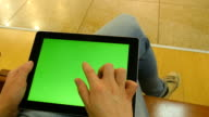 Young girl sitting at bench in shopping mall and working with tablet. Female hands using tablet pc with green screen. Chroma key video
