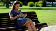 young girl sitting at the bench in a park and  drawing or making notes video