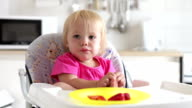 Young Girl Sitting In High Chair Eating Strawberry video