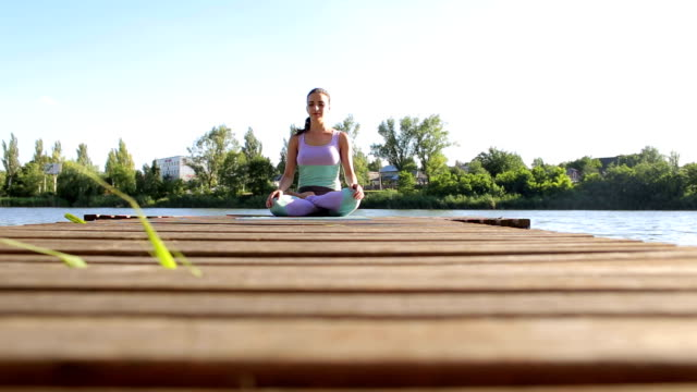 Young girl sitting in Lotus position outdoors.Yoga video