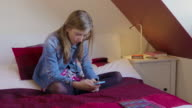 Young girl sitting on bed on smartphone (Hair down) video
