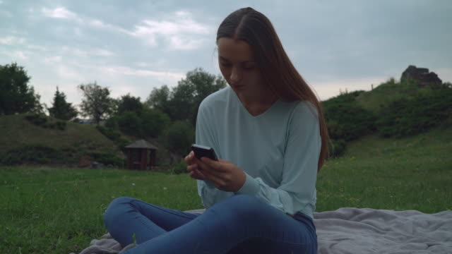A young girl sitting on blankets on the lawn in the park and gaining a message on the phone video