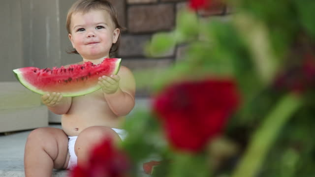 Young girl sitting on porch with watermelon video