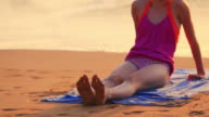 Young girl sitting on tropical beach video