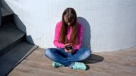 Young girl sitting outside playing with her smart phone video