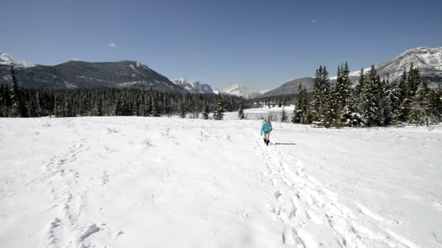 Young girl skips across snowy meadow with skates video
