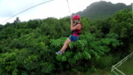 Young girl smiling and screaming when zipling on cable above lush rainforest video